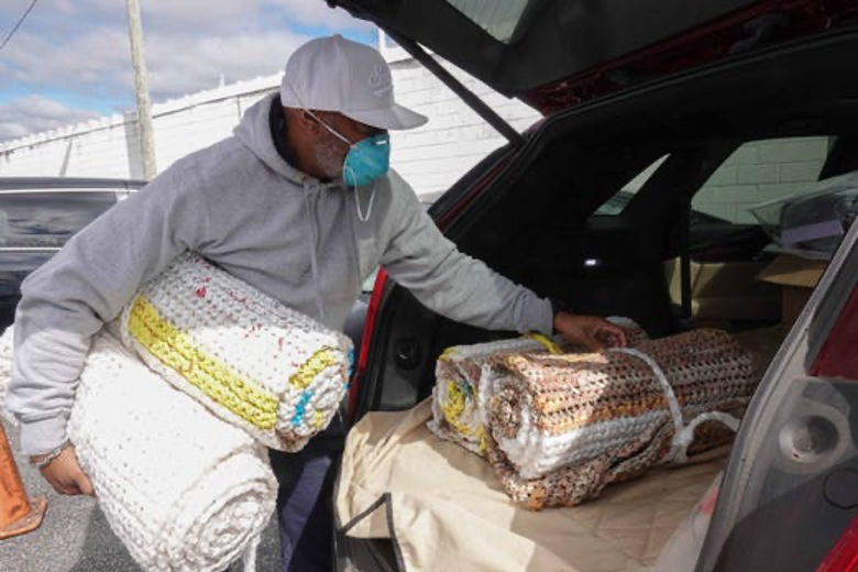 Andre Rider, an outreach coordinator for Brandywine Counseling, helps load donated bed rolls into an outreach van that was taking supplies vulnerable communities in need of assistance in the Dover area during the coronavirus outbreak.